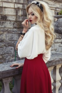 beautiful woman with blond hair in elegant dress at park