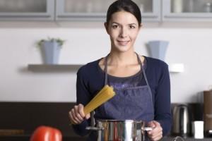 Glückliche Hausfrau kocht Spaghetti